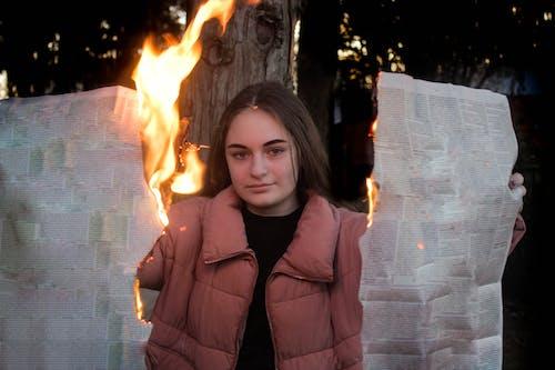 Woman burning newspaper in bright fire near tree