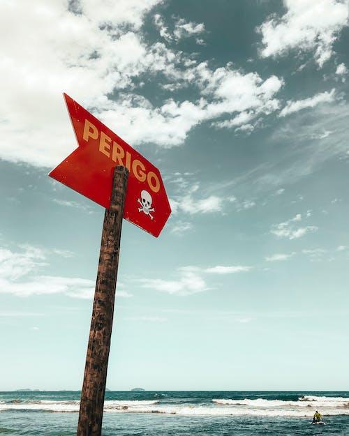 Sign located near waving sea water