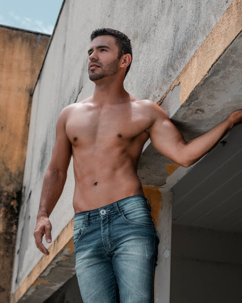 From below of serious ethnic shirtless male in jeans standing near shabby building in sunny day