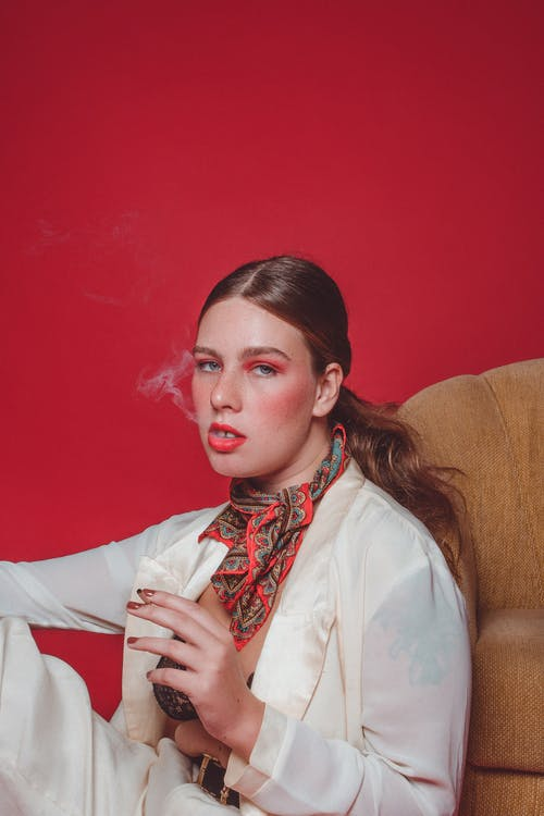 Stylish woman smoking cigarette near red wall