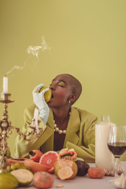 Black woman eating apple and sitting at table