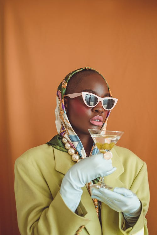 Woman in Yellow Coat Wearing Sunglasses Holding Drinking Glass