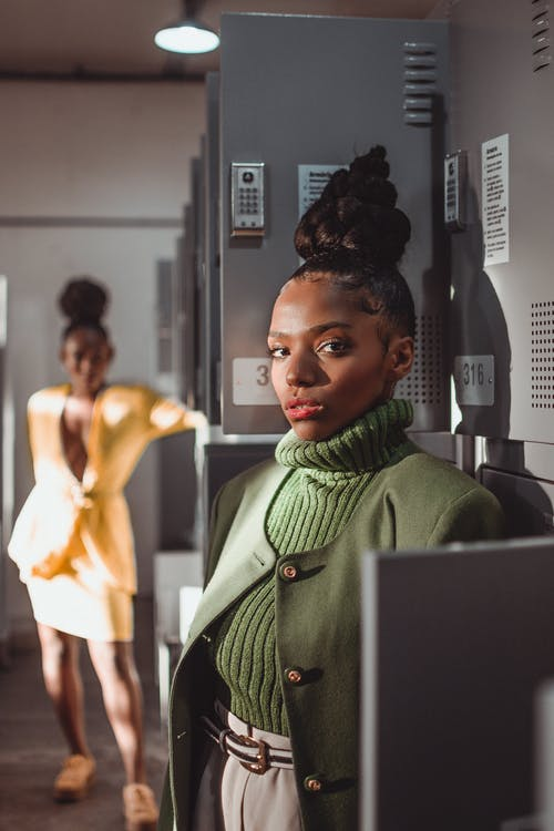 Black woman standing near gray lockers
