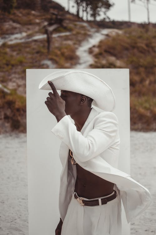 Stylish black man in unbuttoned white jacket and hat