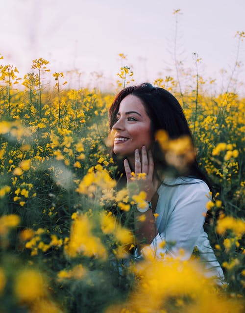 Woman in White Shirt Standing on Yellow Flower Field