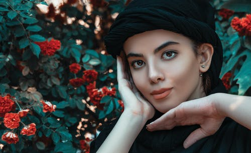 Crop attractive female wearing black turban standing near lush blooming tree in garden and touching face gently while looking at camera contentedly
