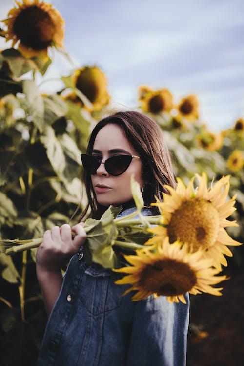 Calm woman standing in sunflower field