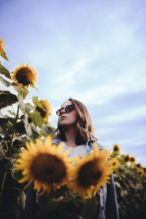 Thoughtful woman standing amidst lush sunflowers