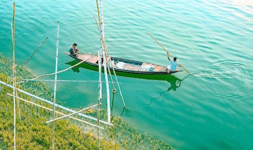 Ethnic men floating on canoe along pure blue lake