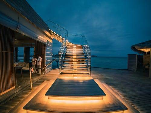 Contemporary tropical resort villa located on seafront with big stylish outdoor staircase and veranda in evening
