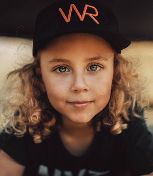 Photo of Girl Smiling While Wearing Black Cap
