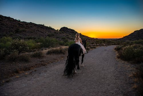 Woman in White Dress Riding Black Horse