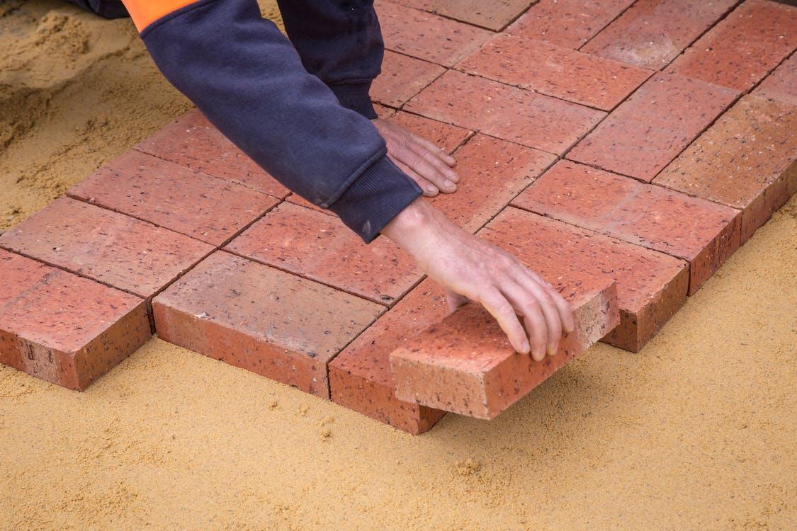 Crop faceless man laying bricks on ground
