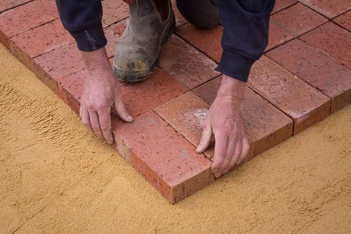 High angle crop anonymous worker in workwear lying bricks on sandy ground in square shape