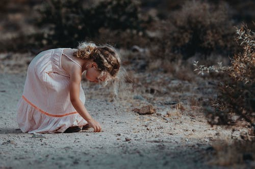 Girl in Pink Dress Picking Up Stone on Ground