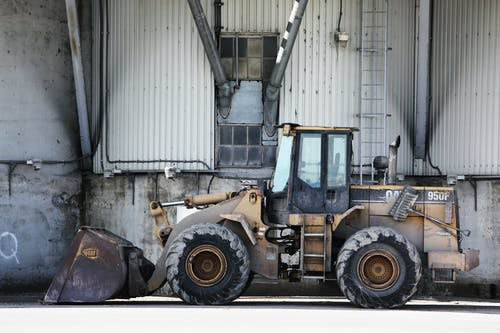 Yellow and Black Payloader Parked Beside Building