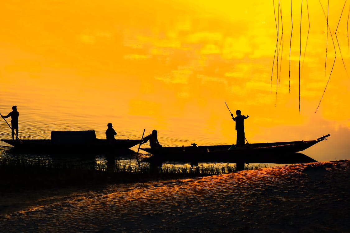 Anonymous fishermen in boat on lake shore at sunset