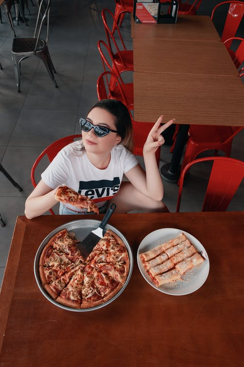 Woman in White Crew Neck T-shirt Holding Sliced of Pizza
