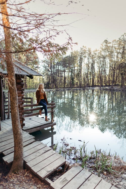 Photo of Woman Sitting on Wooden Dock Near Lake