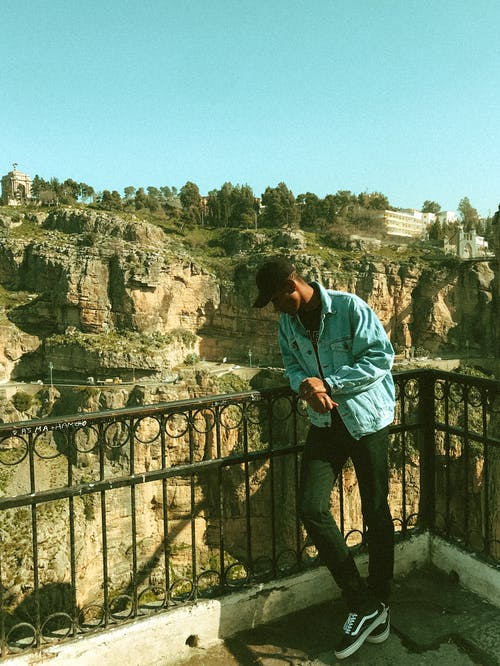 Young ethnic man standing on viewing platform and admiring view of rocky ravine