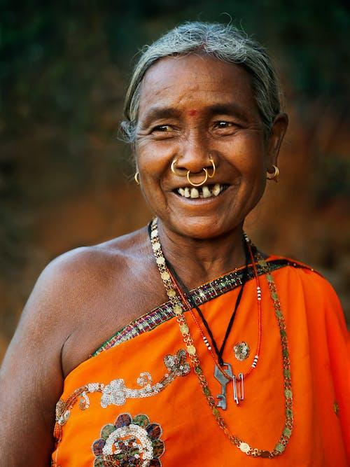 Frau In Orange Blumen ärmelloses Kleid Lächelnd