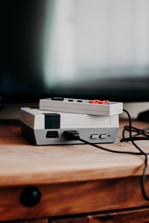 Photo of Video Game Console on Brown Wooden Table