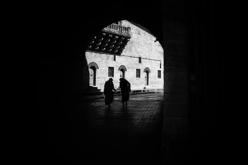 Silhouettes of anonymous ladies walking along arched passage