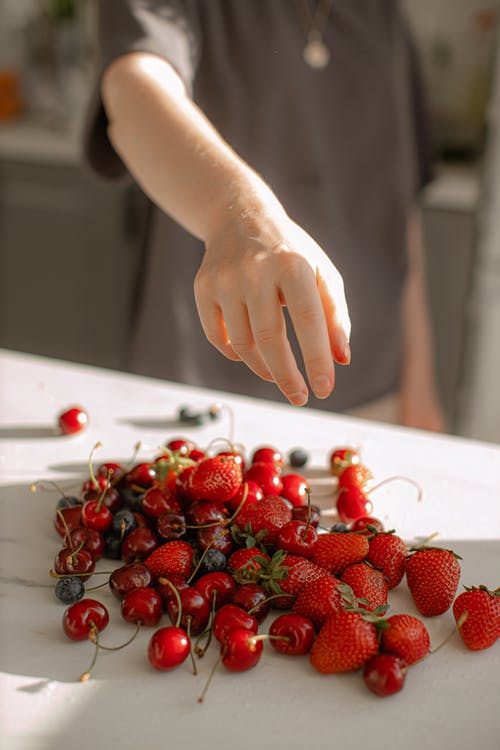 Photo of Person's Hand Over Red Fruits