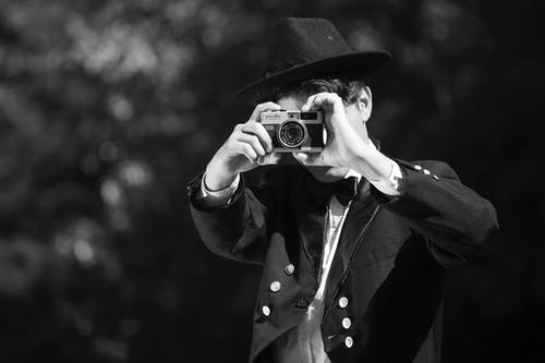 Grayscale Photo of Man in Black Hat and Coat Holding Camera