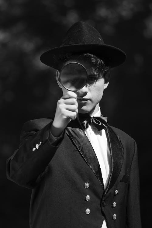 Man in Black Coat Holding Magnifying Lens
