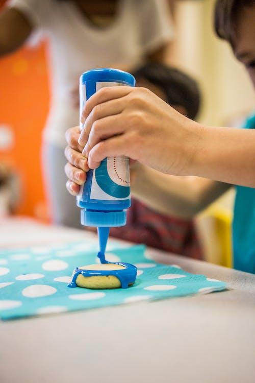 Crop kid decorating biscuit with glaze in studio