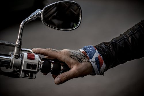 Person's Hand Holding Motorcycle Handlebar
