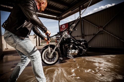 Photo of Man in Black Leather Jacket Cleaning His Motorcycle