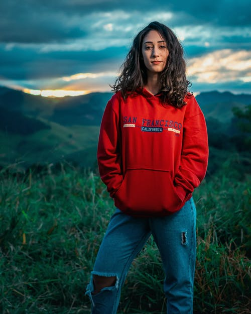 Woman in Red Hoodie Standing on Green Grass Field