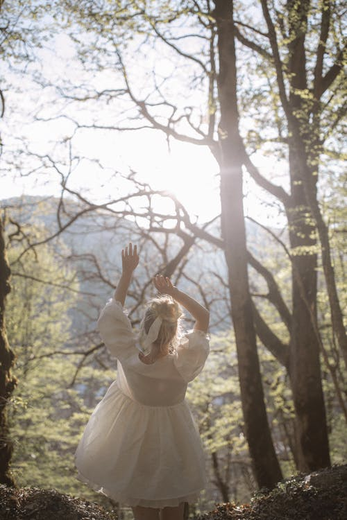 Girl in White Dress Standing on Forest