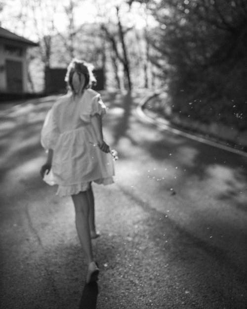 Grayscale Photo of Woman in White Dress Walking