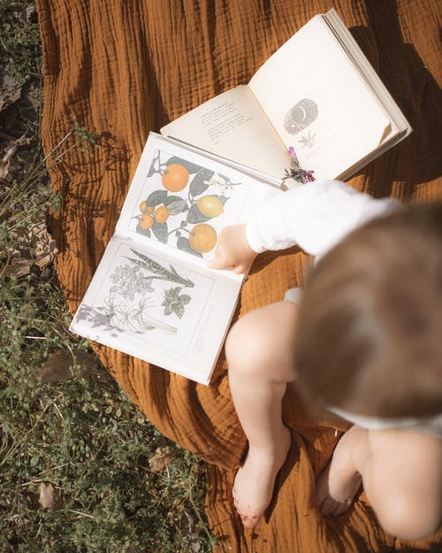 Top View Photo of Baby Sitting Near Open Books