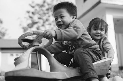 Grayscale Photo of Boy and Girl Playing