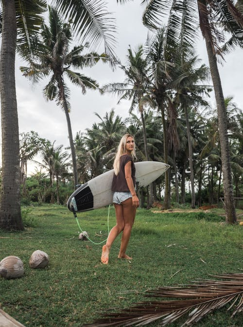 Woman Walking on Grass Field While Holding White Surfboard