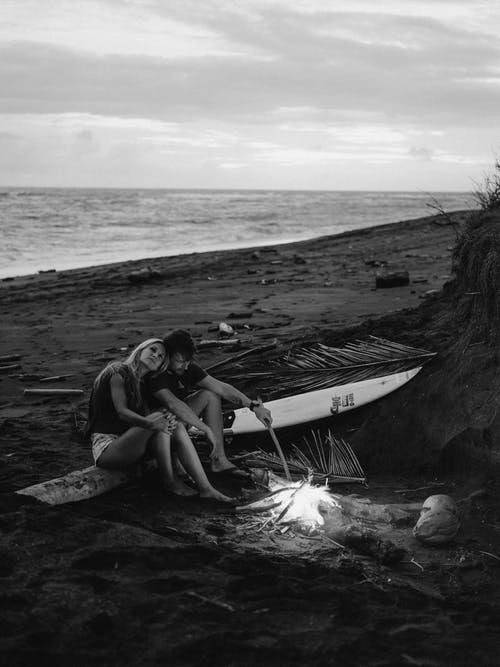 Grayscale Photo of Couple Sitting on Beach Shore