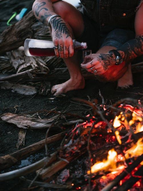 Crop unrecognizable man near bonfire with bottle of drink