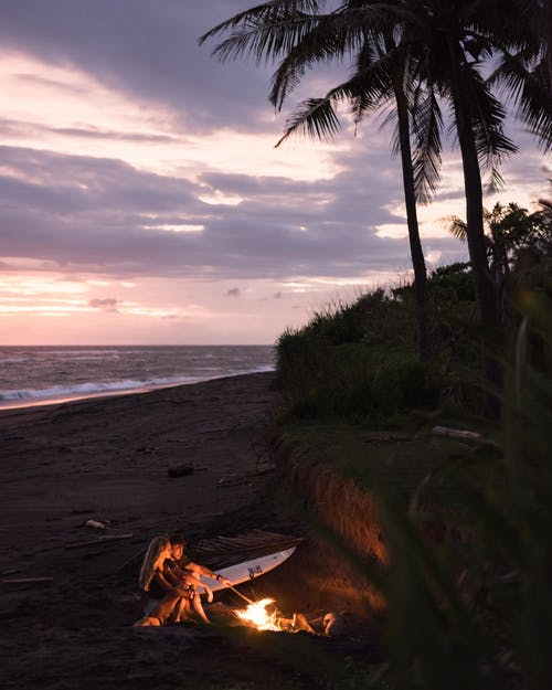 Photo of Couple on Beach Sitting Near Bonfire