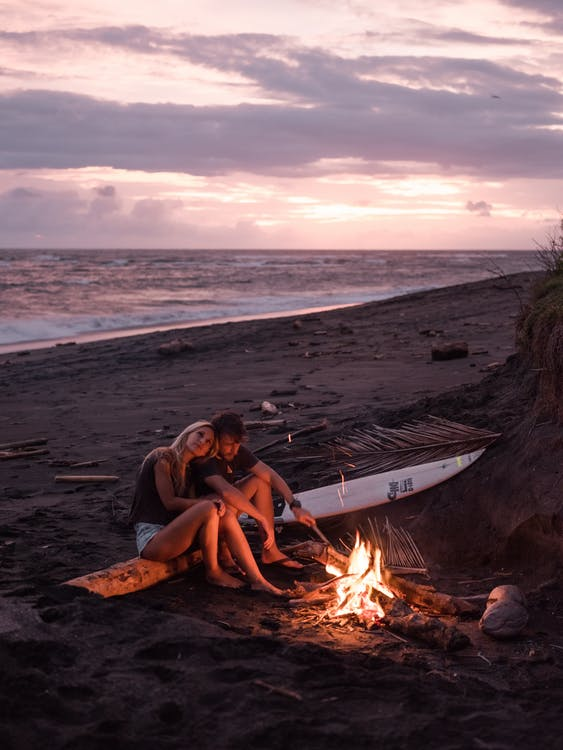 Photo of Couple Sitting on Wooden Log Near Bonfire