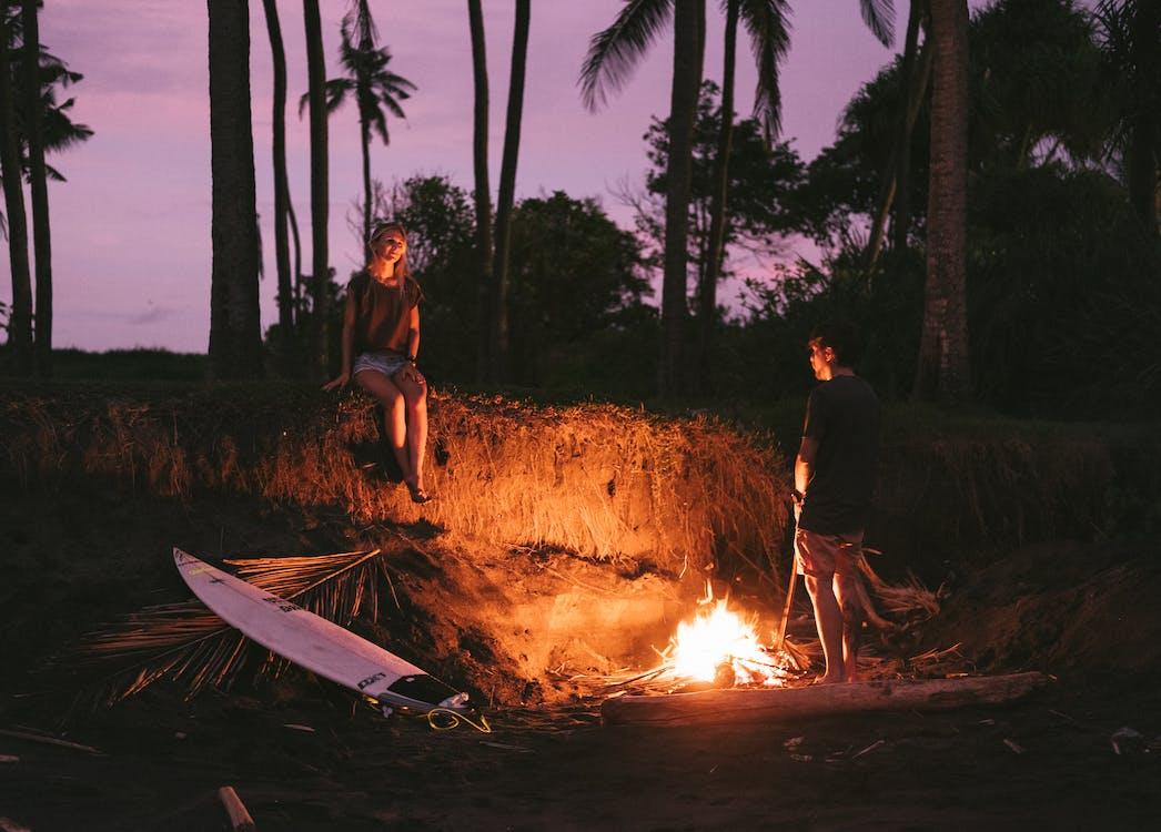 Romantic couple having date on beach near bonfire during ...