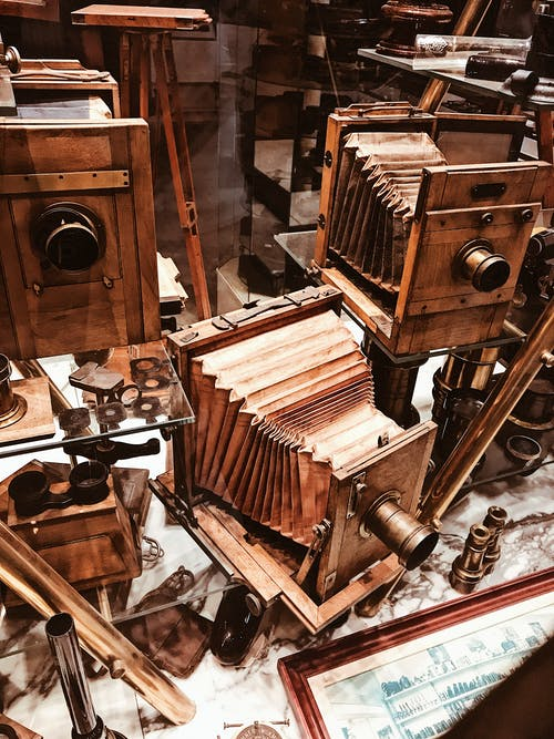 From above collection of various wooden vintage photo cameras placed in showcase of antique shop