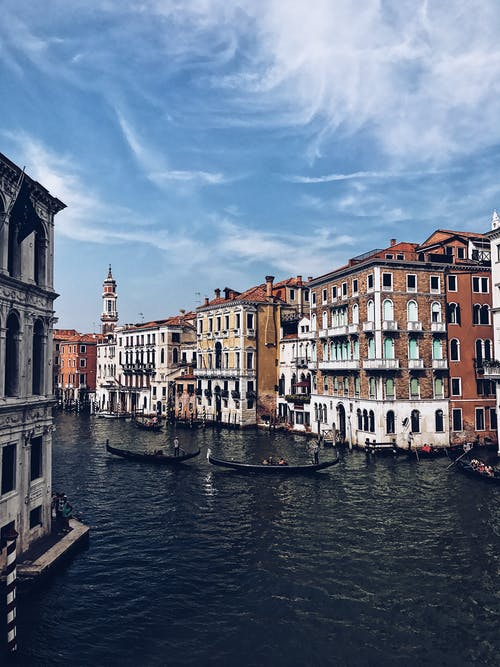 Beautiful view of famous Venice channel with floating gondolas amidst colorful ancient buildings