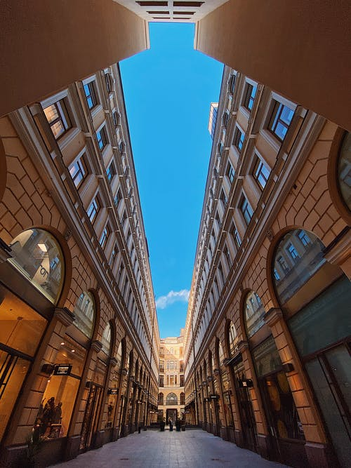 From below of beautiful empty narrow street with contemporary buildings and arched windows against blue sky