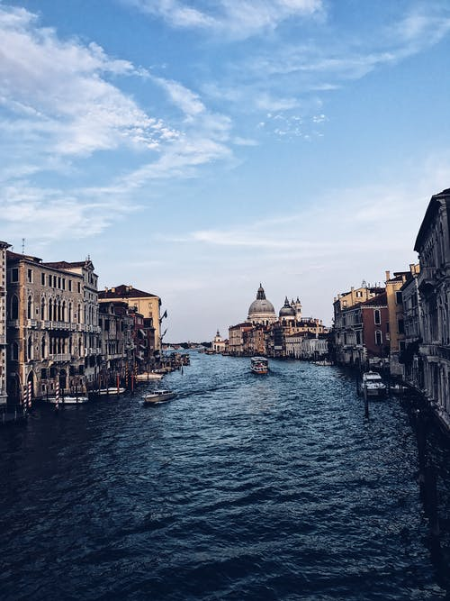 View of Grand Canal with traditional old houses and Basilica Santa Maria della Salute in Venice against blue sky