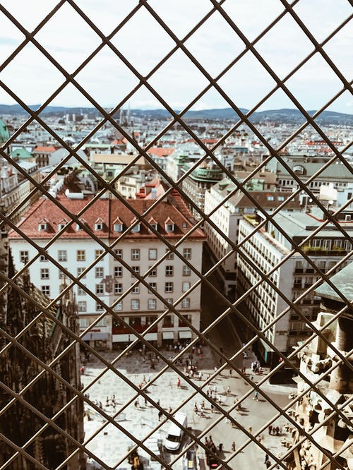 Photo of Chain-Link Fence Against City Background
