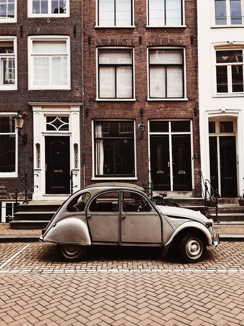 White Volkswagen Beetle Parked Beside Brown Concrete Building